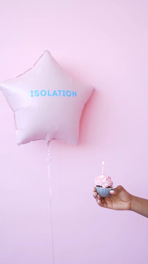 Hand Holding a Cupcake near a Balloon