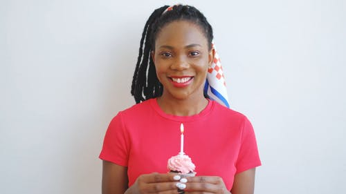 A Woman Blowing A Candle On A Cupcake