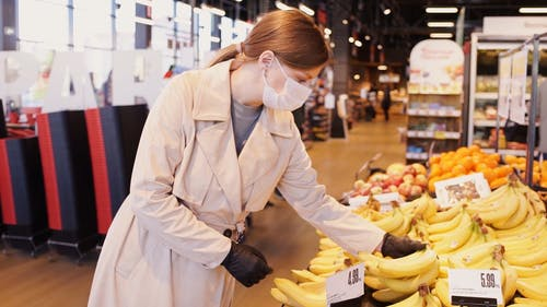 A Woman in the Grocery Store Buying Banana