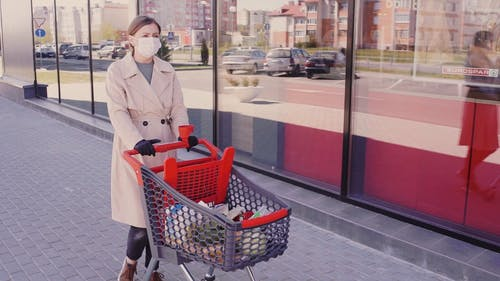 A Woman with a Shopping Cart Walking on the Sidewalk