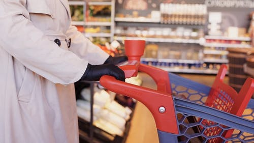 Person in Trench Coat and Black Gloves Pushing a Shopping Cart