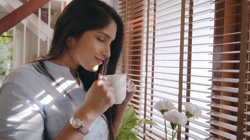 A Woman Smelling Her Coffee In The Morning