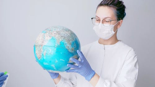 Woman with Face Mask and Latex Gloves Holding a Globe