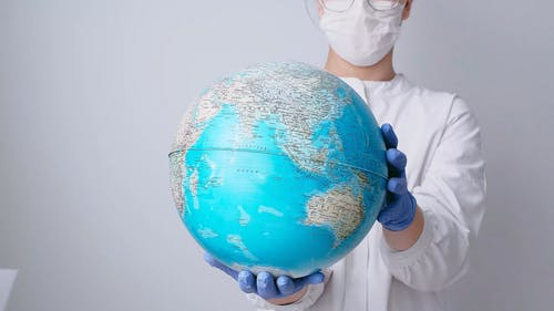Person With Face Mask and Latex Gloves Holding a Globe