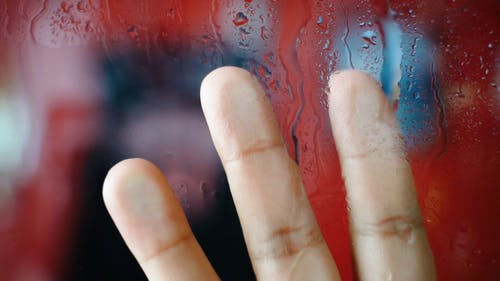 A Close Up Shot of a Hand on a Wet Glass