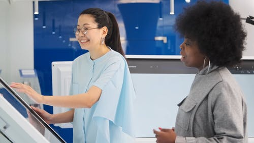women-having-a-conversation-with-the-touchscreen-monitor