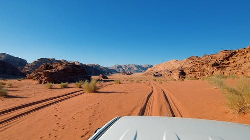 A Desert land With Vehicle Driving Under Blue Sky