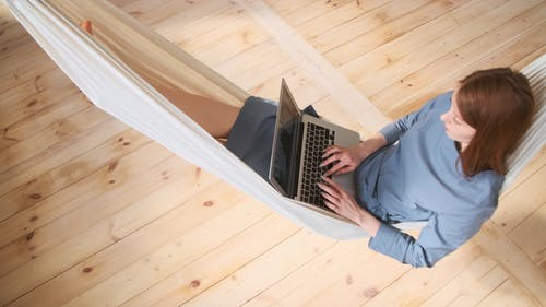 A Woman Typing On A Laptop While Relaxing In A Hammock
