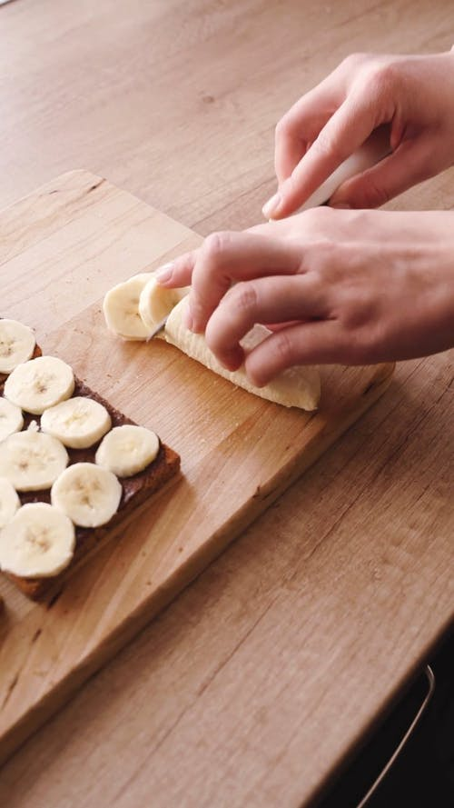A Person Slicing Bananas for the Sandwich