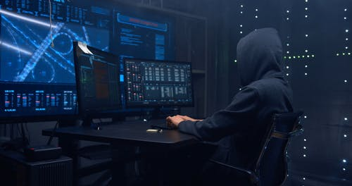 A Person Wearing Hoody Typing on the Keyboard