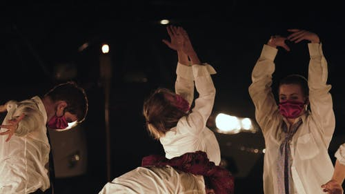 A Dance Group Dancing Outdoor At Night