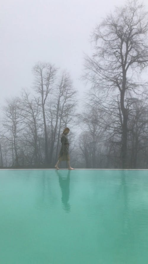 A Woman Walking on the Edge of the Swimming Pool