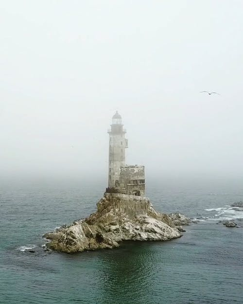 A Shot of an Old Lighthouse by the Rocky Coastal Area