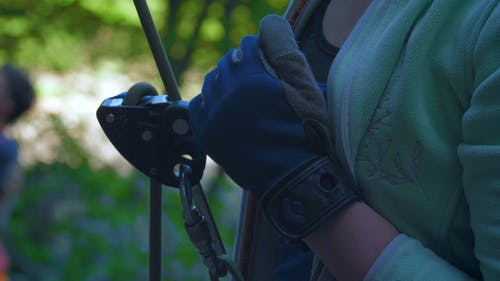 Person Wearing Gloves Holding the Belay Device