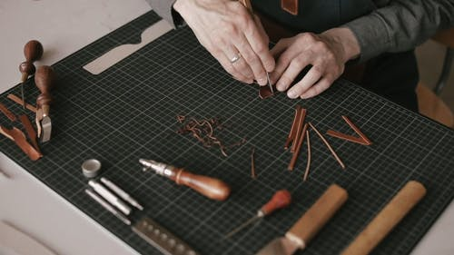A Person Cutting the Leather