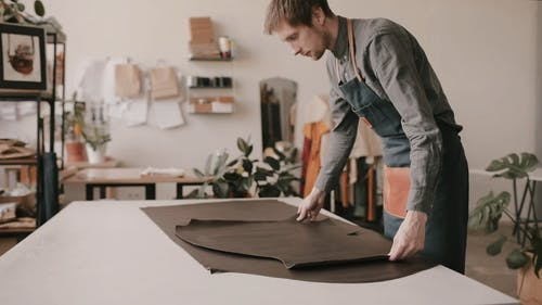 A Man Rolling Out the Leather on the Table