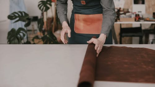 A Leather Worker Spreading The Roll Of Leather On The Table