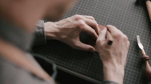A Person Cutting a Piece of Leather