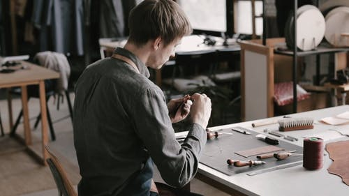 Man Sewing Leather Pieces
