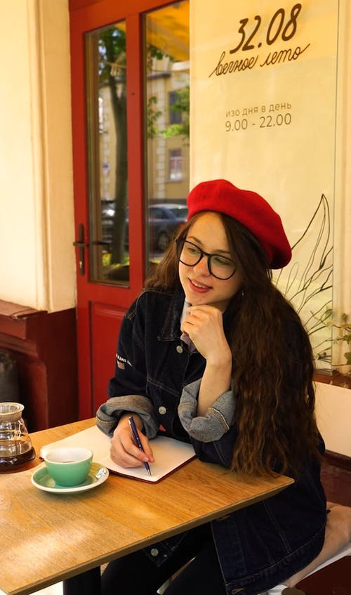 Woman Drinking Coffee and Happily Writing on Her Notebook