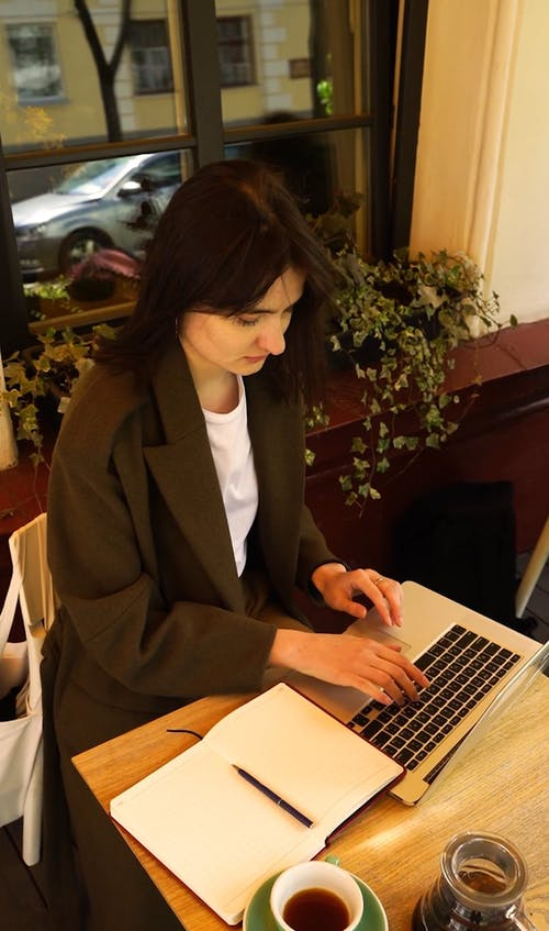 Woman Typing on Her Laptop and Drinking Coffee