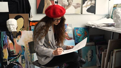 Woman Sitting on a Chair While Drawing on a White Paper
