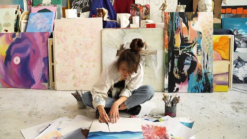 Woman Sitting on a Floor While Painting on Her Canvas