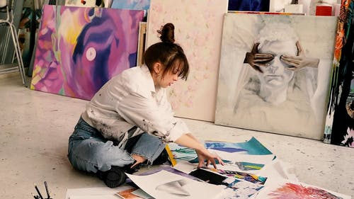 Woman Sitting on a Floor While Drawing on a White Paper