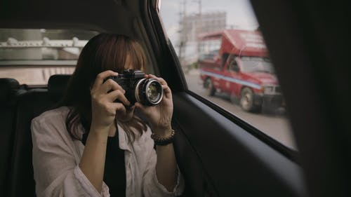 Woman Taking Photo while In the Car