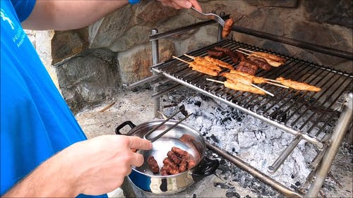 Man Cooking Sausages on the Grill