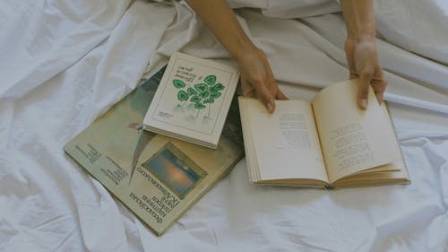 Person with Books on the Bed