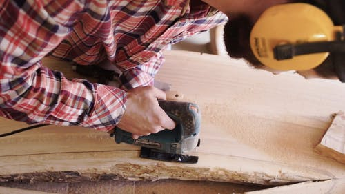 A Carpenter Cutting Away The Damaged Part Of A Wooden Board