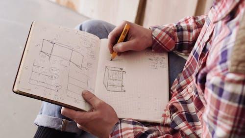 A Carpenter Making Sketches Of Furnitures