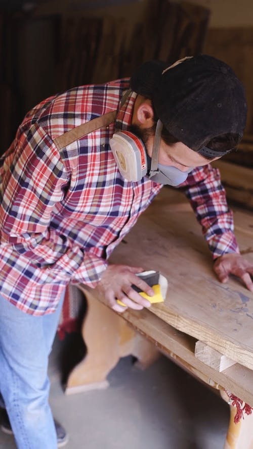 A Man Smoothing The Wood Edges Using A Sand Paper