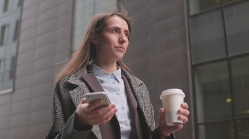 Woman Holding Her Phone and Drinking Coffee