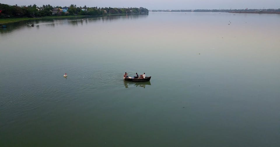 People In A Rowboat Across The River