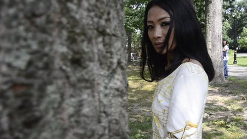 Woman Walking Behind the Tree