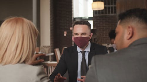 A Man Wearing a Mask In A Meeting