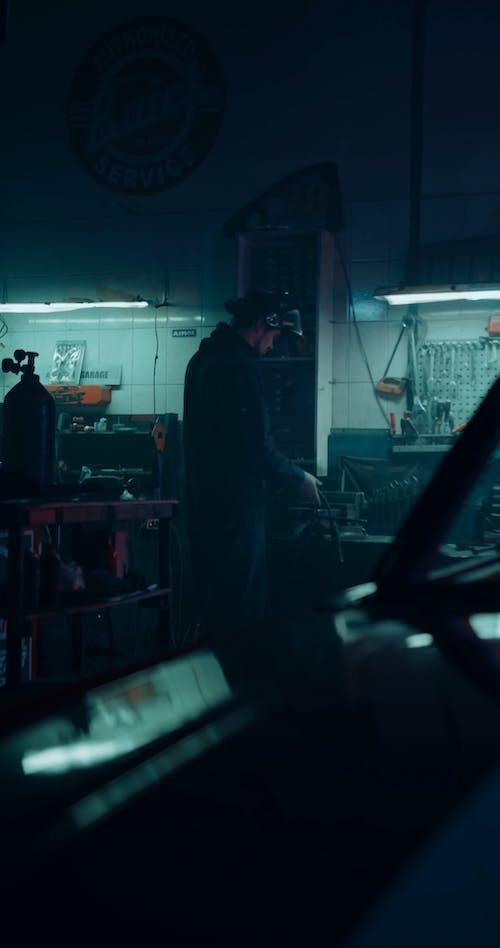 A Man Welding A Metal Piece Inside A Motor Shop