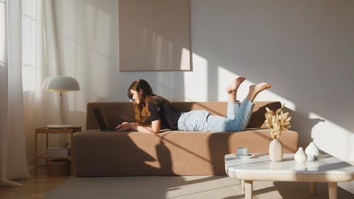 A Woman Working On A Laptop In A Couch