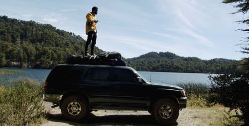 Man Standing on Top of His Car