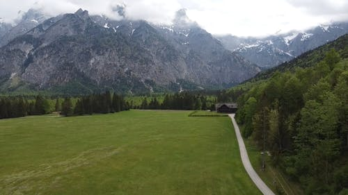 Drone Flying Over A Grass Field With The Mountains As Backdrop