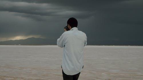 Man Walking while Taking Photo