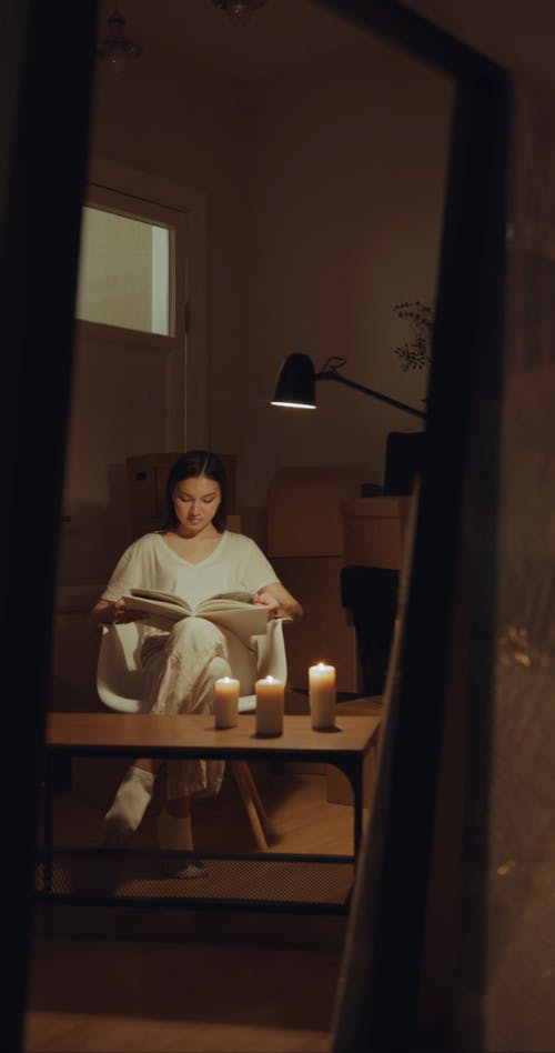 A Woman Reading A Book Under The Lamp Light