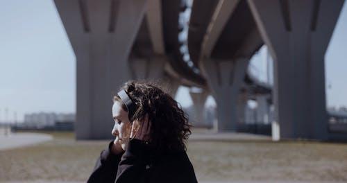 A Woman Wearing A Headphone Dancing Under The Bridge