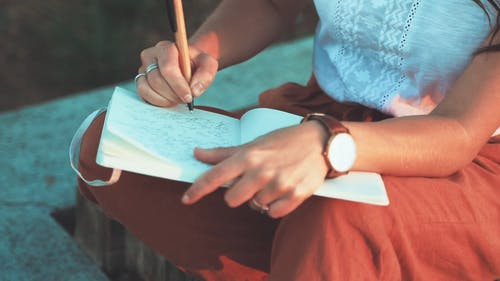 A Woman Writing On A Journal