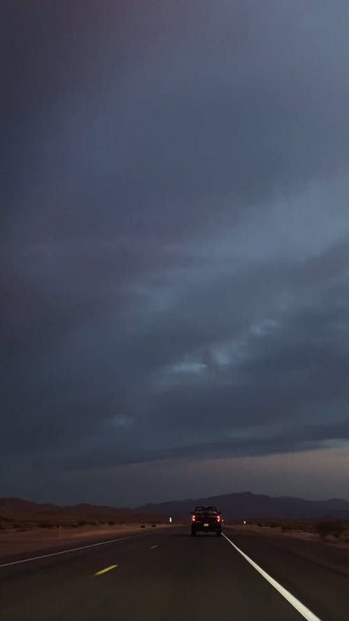 Vehicle Traveling on Roadway Under Dark Sky