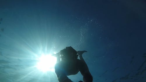 Man Swimming Underwater With Camera