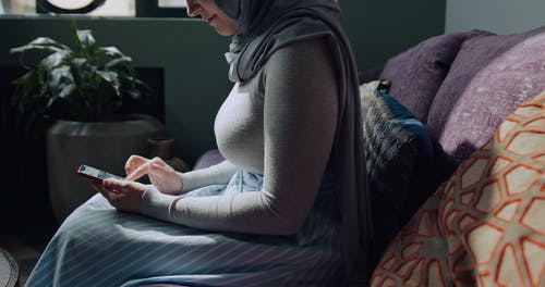 A Woman Using Her Cellphone At Home
