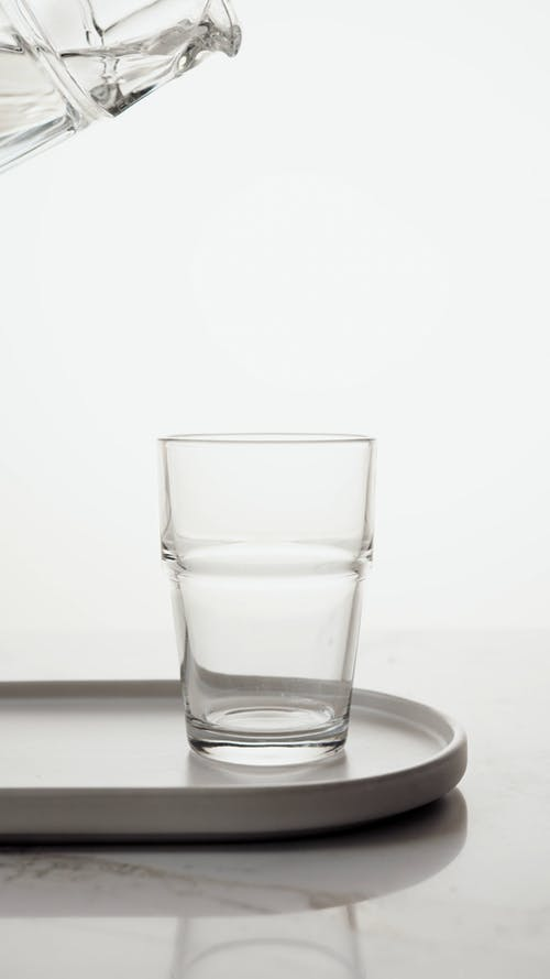 A Person Pouring Water in the Glass